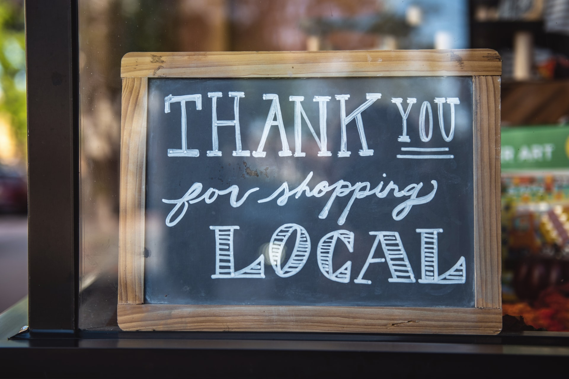 Store sign with the message Thank you for shopping local written on it